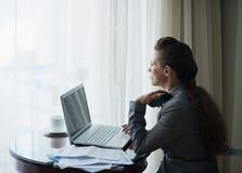 Στοχαστική επιχειρησιακή γυναίκα που εργάζεται στο δωμάτιο ξενοδοχείου στοκ φωτογραφίες με δικαίωμα ελεύθερης χρήσης