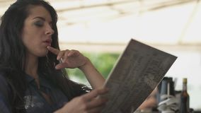 Στοχαστική εύθυμη γυναίκα που φαίνεται επιλογές στο εστιατόριο και που διορθώνει την τρίχα της Μόνο κορίτσι που στηρίζεται σε ένα απόθεμα βίντεο
