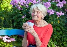 Στοχαστική ηλικιωμένη γυναίκα με τον καφέ στον κήπο στοκ φωτογραφία