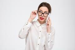 Στοχαστική καλή επιχειρηματίας στα γυαλιά που μιλούν στο τηλέφωνο κυττάρων στοκ φωτογραφία με δικαίωμα ελεύθερης χρήσης