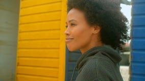 Στοχαστική νέα γυναίκα αφροαμερικάνων που περπατά στην καλύβα παραλιών απόθεμα βίντεο