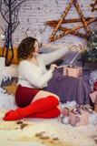 Στοχαστική νέα γυναίκα με το παρόν κιβώτιο κοντά στο χριστουγεννιάτικο δέντρο Στοκ Εικόνες