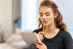 Στοχαστική νέα γυναίκα που κάνει τις σημειώσεις που χρησιμοποιούν το σημειωματάριο στην κουζίνα στοκ φωτογραφία με δικαίωμα ελεύθερης χρήσης