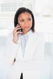 Στοχαστική νέα μελαχροινή μαλλιαρή επιχειρηματίας που κάνει ένα τηλεφώνημα Στοκ εικόνες με δικαίωμα ελεύθερης χρήσης
