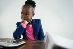 Στοχαστική σοβαρή επιχειρηματίας που εξετάζει τον υπολογιστή Στοκ εικόνα με δικαίωμα ελεύθερης χρήσης