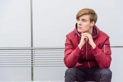 Στοχαστική συνεδρίαση αγοριών υπαίθρια στο πορτρέτο πάγκων πέρα από την αστική πλάτη Στοκ Εικόνες