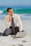 Στοχαστική συνεδρίαση επιχειρηματιών στην άμμο με το lap-top του Στοκ Εικόνες