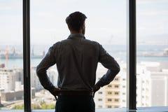 Στοχαστικός αρσενικός ανώτερος υπάλληλος που κοιτάζει μέσω του παραθύρου στην αρχή Στοκ Φωτογραφίες