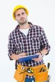 Στοχαστικός αρσενικός επισκευαστής που γράφει στην περιοχή αποκομμάτων Στοκ φωτογραφία με δικαίωμα ελεύθερης χρήσης