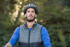 Στοχαστικός αρσενικός ποδηλάτης στο δάσος Στοκ φωτογραφίες με δικαίωμα ελεύθερης χρήσης