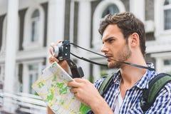 Στοχαστικός αρσενικός τουρίστας που χρησιμοποιεί τη κάμερα στην πόλη Στοκ φωτογραφίες με δικαίωμα ελεύθερης χρήσης