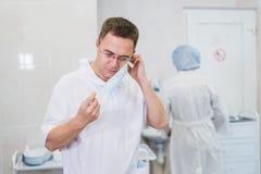 Στοχαστικός αρσενικός χειρούργος που φορά τη χειρουργική μάσκα στο νοσοκομείο Στοκ Φωτογραφία