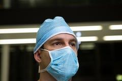 Στοχαστικός αρσενικός χειρούργος που φορά τη χειρουργική μάσκα Στοκ φωτογραφία με δικαίωμα ελεύθερης χρήσης