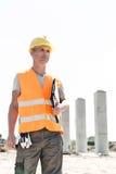 Στοχαστικός αρχιτέκτονας που κοιτάζει μακριά κρατώντας την περιοχή αποκομμάτων στο εργοτάξιο οικοδομής Στοκ Εικόνες