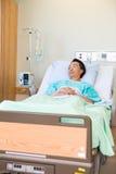 Στοχαστικός ασθενής που βρίσκεται στο κρεβάτι στο νοσοκομείο Στοκ Εικόνες