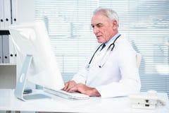 Στοχαστικός γιατρός που εργάζεται στον υπολογιστή Στοκ εικόνες με δικαίωμα ελεύθερης χρήσης