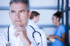 Στοχαστικός γιατρός που στέκεται στο νοσοκομείο στοκ φωτογραφίες με δικαίωμα ελεύθερης χρήσης