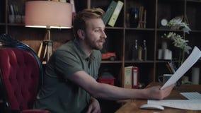 Στοχαστικός δημιουργικός σχεδιαστής που εξετάζει το έγγραφο και που σκέφτεται για το νέο πρόγραμμα απόθεμα βίντεο