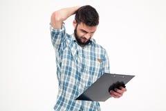 Στοχαστικός ενοχλημένος γενειοφόρος νεαρός άνδρας που γρατσουνίζει το κεφάλι του με το χέρι Στοκ Φωτογραφίες