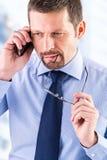 Στοχαστικός επιχειρηματίας που κάνει ένα τηλεφώνημα Στοκ Εικόνες