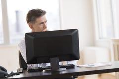 Στοχαστικός επιχειρηματίας που κοιτάζει μακριά καθμένος στο γραφείο μέσα μακριά Στοκ Εικόνες