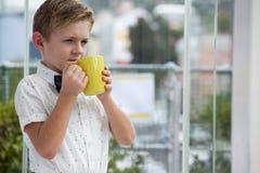 Στοχαστικός επιχειρηματίας που κοιτάζει μακριά κρατώντας την κίτρινη κούπα καφέ Στοκ εικόνα με δικαίωμα ελεύθερης χρήσης