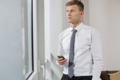 Στοχαστικός επιχειρηματίας που κρατά το έξυπνο τηλέφωνο κοιτάζοντας μέσω του παραθύρου στο σπίτι Στοκ φωτογραφία με δικαίωμα ελεύθερης χρήσης
