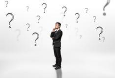 Στοχαστικός επιχειρηματίας που φαίνεται προς τα πάνω από τα ερωτηματικά στο άσπρο υπόβαθρο Στοκ Εικόνες