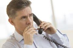 Στοχαστικός επιχειρηματίας που χρησιμοποιεί το τηλέφωνο γραμμών εδάφους στην αρχή Στοκ Εικόνες