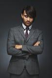 Στοχαστικός επιχειρηματίας στο κοστούμι που στέκεται στο μαύρο κλίμα Στοκ εικόνα με δικαίωμα ελεύθερης χρήσης