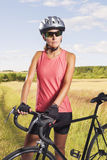 Στοχαστικός θηλυκός ποδηλάτης που ένα ποδήλατο. αθλητής που εξοπλίζεται με τις δημόσιες σχέσεις Στοκ Φωτογραφία