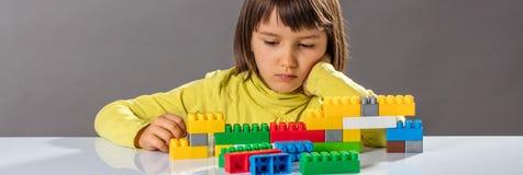 Στοχαστικός λίγο παιδί που εξετάζει την τούβλα οικοδόμησης με τη φαντασία στοκ εικόνες