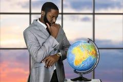 Στοχαστικός μαύρος επιχειρηματίας με τη σφαίρα Στοκ Εικόνα