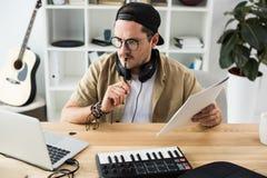 Στοχαστικός μουσικός που εξετάζει το lap-top στοκ φωτογραφίες