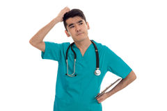 Στοχαστικός νέος αρσενικός γιατρός σε ομοιόμορφο με την τοποθέτηση stathoscope που απομονώνεται στο άσπρο υπόβαθρο Στοκ Φωτογραφίες