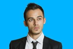 Στοχαστικός νέος επιχειρηματίας που κοιτάζει μακριά πέρα από το χρωματισμένο υπόβαθρο Στοκ Φωτογραφίες