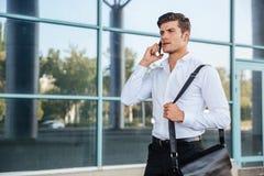 Στοχαστικός νέος επιχειρηματίας που μιλά στο τηλέφωνο υπαίθρια Στοκ Εικόνα