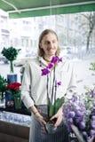 Στοχαστικός νέος κηπουρός που παρουσιάζει το unordinary λουλούδι για τους πελάτες στοκ εικόνα