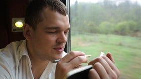 Στοχαστικός νεαρός άνδρας που παίρνει τις σημειώσεις στο τραίνο φιλμ μικρού μήκους