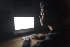 Στοχαστικός νεαρός άνδρας που χρησιμοποιεί τον κενό υπολογιστή οθόνης στο σκοτεινό δωμάτιο στοκ φωτογραφία