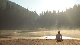 Στοχαστικός νεαρός άνδρας στα παραδοσιακά ουκρανικά ενδύματα που κάθεται στη δύσκολη ακτή της λίμνης Synevir Carpathians και απόθεμα βίντεο