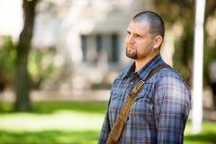 Στοχαστικός σπουδαστής που στέκεται στην πανεπιστημιούπολη Στοκ Εικόνες