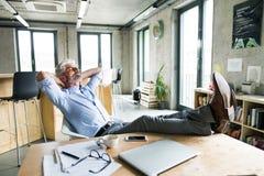 Στοχαστικός ώριμος επιχειρηματίας με το smartphone στο γραφείο Στοκ εικόνα με δικαίωμα ελεύθερης χρήσης