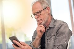 Στοχαστικό άτομο που εξετάζει το τηλέφωνο της Mobil του, ελαφριά επίδραση Στοκ Εικόνες