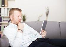 Στοχαστικό άτομο που διαβάζει τον υπολογιστή ταμπλετών του Στοκ φωτογραφία με δικαίωμα ελεύθερης χρήσης