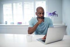 Στοχαστικό άτομο που χρησιμοποιεί το lap-top Στοκ φωτογραφία με δικαίωμα ελεύθερης χρήσης