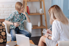 Στοχαστικό αγόρι που ακούει το θηλυκό ψυχολόγο Στοκ Φωτογραφία