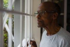 Στοχαστικό ανώτερο άτομο που φορά eyeglasses κοιτάζοντας έξω μέσω του παραθύρου Στοκ εικόνα με δικαίωμα ελεύθερης χρήσης