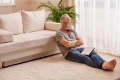 Στοχαστικό ανώτερο γενειοφόρο άτομο με την ψηφιακή ταμπλέτα που εξετάζει το παράθυρο και που κάθεται στο πάτωμα Στοκ Φωτογραφία