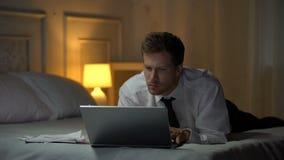 Στοχαστικό αρσενικό που βρίσκεται στο κρεβάτι και που διαβάζει τα έγγραφα σχετικά με το lap-top, επιχειρησιακό ηλεκτρονικό ταχυδρ απόθεμα βίντεο